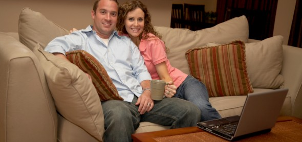Happy couple on couch smiling